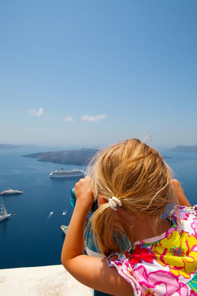 Девочка смотрит на паромы в Санторини