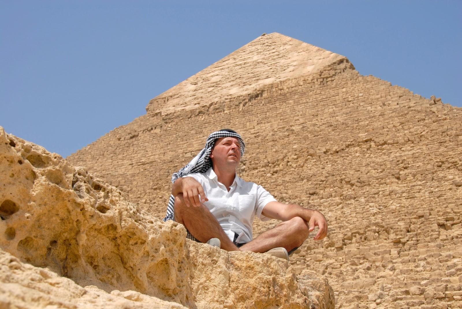 Человек отдыхает на фоне пирамиды в Египте